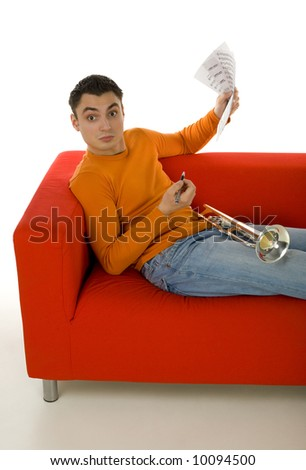 Trumpeter sitting on red couch and composing music, holding sheet music in hands.  Looking at camera. White background.
