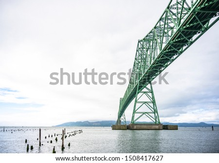 Truss elevated arched long Astoria–Megler bridge in Astoria city across the mouth of the Columbia River at the Pacific ocean coast and rotten remains of wooden pillars of an old destroyed pier #1508417627