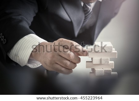 Trust business concept: Businessman choosing the wood block on blurred office background.