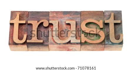 trust word in vintage wooden letterpress printing blocks, stained by color inks, isolated on white