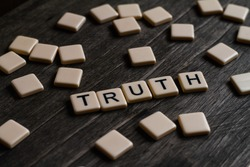 Truth affirmation spelt out using tiles on a timber surface