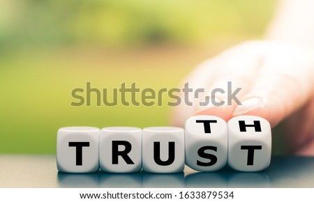 """Truth instead of trust. Hand turns dice and changes the word """"Trust"""" to """"Truth""""."""