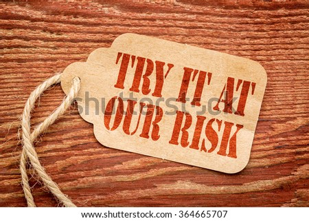 Try it at our risk - red stencil text on a paper price tag against rustic wood #364665707