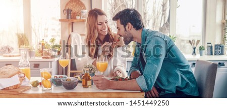 Try it! Beautiful young couple enjoying healthy breakfast while sitting in the kitchen at home
