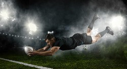 Try.  Rugby football player in action on dark arena background