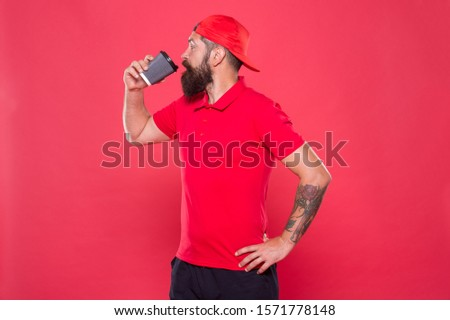 try the taste. bearded man drink morning coffee. brutal stylish barista. energy concept. hipster barista red background. barista job. coffee shop advertisement. take away drink. be active whole day.
