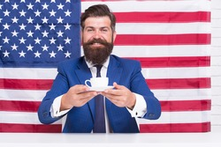 try this. drinking coffee on tribune. american politician in election. his election campaign. bearded man drink coffee cup. American education reform in july 4. American citizen at USA flag.
