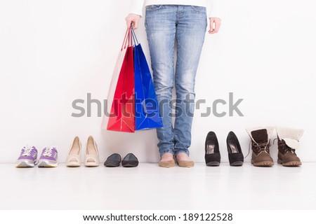 Trying on Shoes. Woman stands in a pair of open toe shoes with many other options on the floor