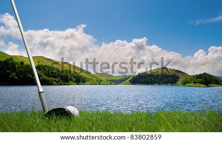 trying to hit a golf ball with club over a lake