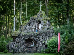 Trzebnica, Poland - August 29, 2021: A stone cave with altar of Saint Mary, surrounded with forest, in front of a church of the Fourteen Holy Helpers.