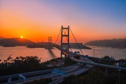 Tsing Ma bridge double-decked suspension bridge between Ma Wan island and Tsing Yi island at sunset in Hong Kong.