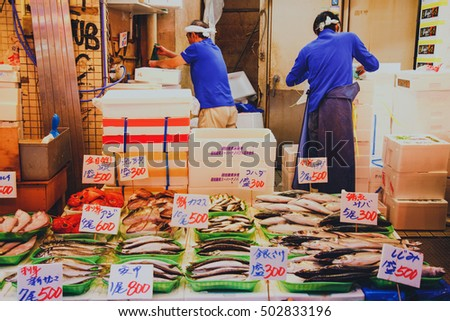 Photo of  Tsukiji, Tokyo, Japan - October 24, 2016 : Japanese fishmonger preparing and packing fish into foam box at Tsukiji Fish Market in Tokyo, Japan. film style photo