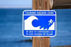 Tsunami Hazard Zone warning sign on ocean coast warns the public about possible danger after an earthquake. Close up. Blurred blue ocean water in background