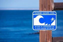 Tsunami Hazard Zone warning sign on the Pacific Ocean coast warn the public about possible danger after an earthquake. Blurred blue ocean surface on horizon