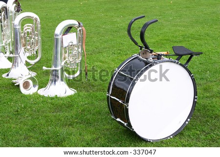 Tubas, bass drum and a cornet or trumpet on the grass as a brass band takes a break during a village fair.
