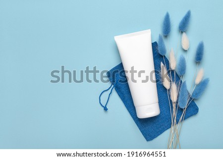 Tube container for cosmetic cream for hands, feet or face, toothpaste on cloth bag. Cleaning, care and maintenance concept. Studio shot with copy space, empty, blank. Сток-фото ©