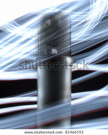 Tube microphone, isolated on black background with light effects.