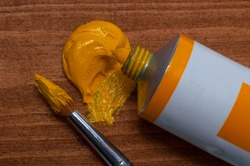 Tube of yellow oil paint and brush on wooden background