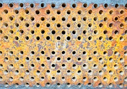 Tube sheet or plate of heat exchanger or boiler closeup texture vibrant colors background opened for inspection maintenance or cleaning from insoluble hard mineral deposits salts scale and corrosion.