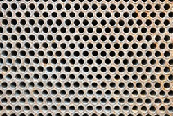 Tube sheet or plate of heat exchanger or boiler closeup texture vibrant colors background opened for inspection maintenance cleaning from insoluble hard mineral deposits salts scale and corrosion.