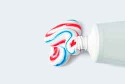 Tube with toothpaste isolated on light background, top view. Tricolor toothpaste, copy space