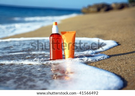 Tubes with sun protection in waves on beach of ocean