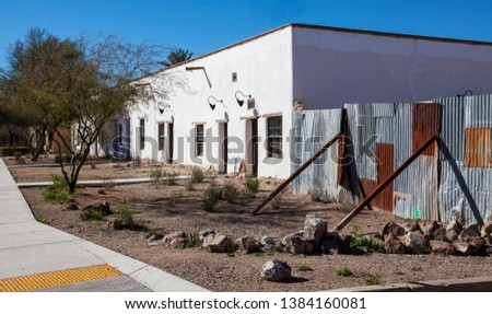 Tucson, Arizona vintage adobe building with propped up rusty steel fencing.
