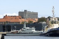 Tug and military ship in Fredericia harbour close to the city with big grey hospital in the background.