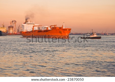 Tug and tanker on the river in orange sunset