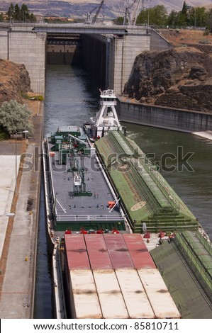 Tug boat and cargo barge exits a lock