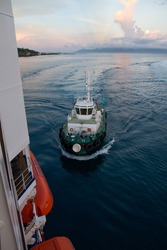 Tug boat guiding a tourist ship into port at Tahiti in the early morning.