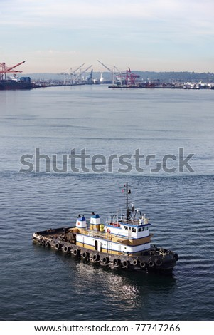Tug boat in Elliot Bay with Port of Seattle in the background