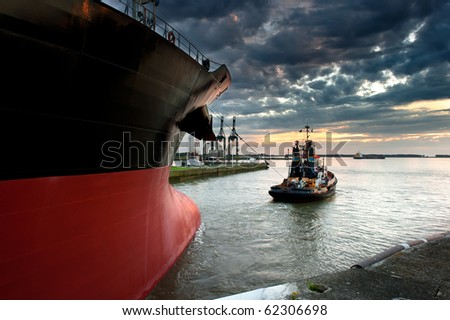 Tug boat taking out the ship from the harbor