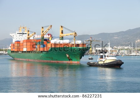 tug boat towing container ship in harbor