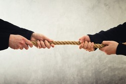 Tug of war. Female hands pulling rope to opposite sides. Rivalry concept.
