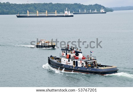 Tugboat and Pilot boat in the Panama Channel with two cargo ships moving in the background