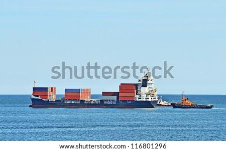 Tugboat assisting cargo ship over lighthouse in Odessa, Ukraine