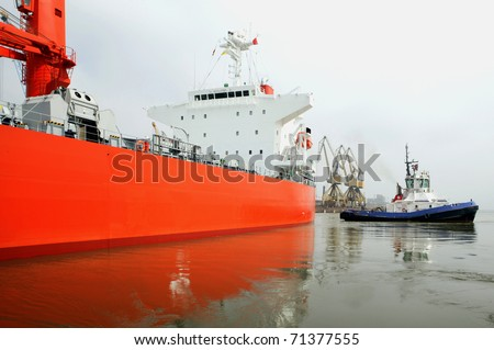Tugboat at work. Oil and gas supertanker