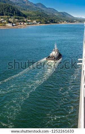 Tugboat guiding cruise ship in to port, Gastineau Channel, Juneau, Alaska, USA.