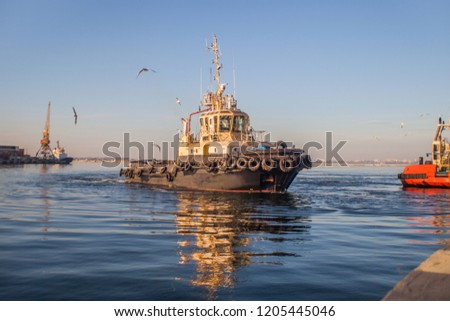 Tugboat Maneuvers, tugboat on maneuvers at sea. Tugboat sailing in the sea. Tugboat making maneuvers. Offshore supply boat in a calm weather day