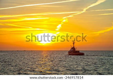 Tugboat on sea in the rays of the setting sun.