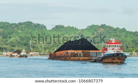 tugboat pulling heavy loaded barge of black coal in the Mahakam river, Indonesia. mining and transportation industry concept
