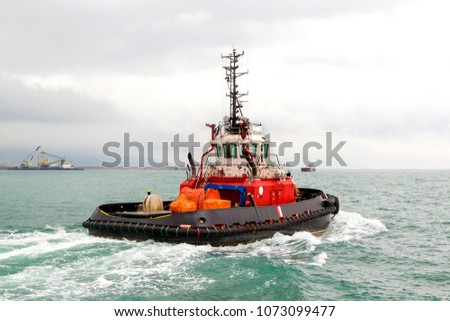 Tugboat sailing in the sea. Tugboat making maneuvers