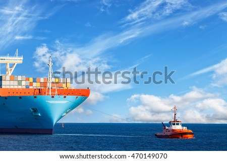 Tugboat towing a large container ship on sea.