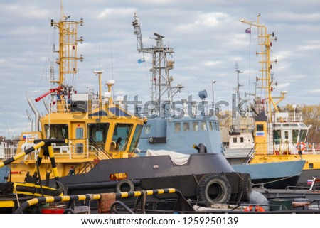 Tugboats and other marine support vessels in port. #1259250139