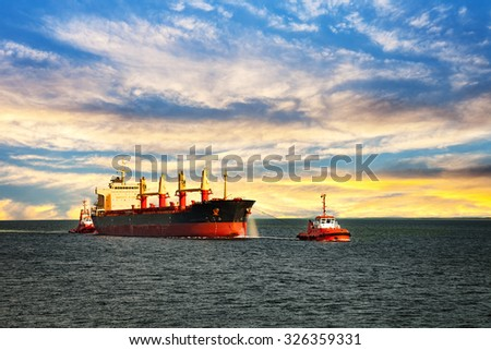Tugboats assisting cargo ship sea in the morning.