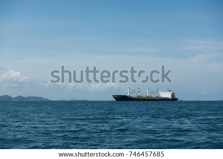 Tugboats assisting container cargo ship to harbor