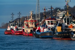 Tugboats in the Harbour of Hamburg Germany waiting for big ships to be helped and pulled, fire fighter boat, pilots and navigator guide for captains