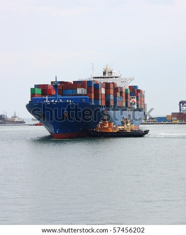 tugboats pulling a container vessel