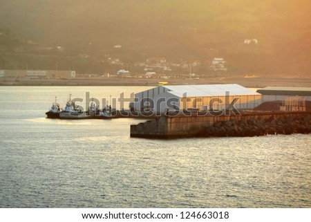 tugboats waiting in port with sunset light